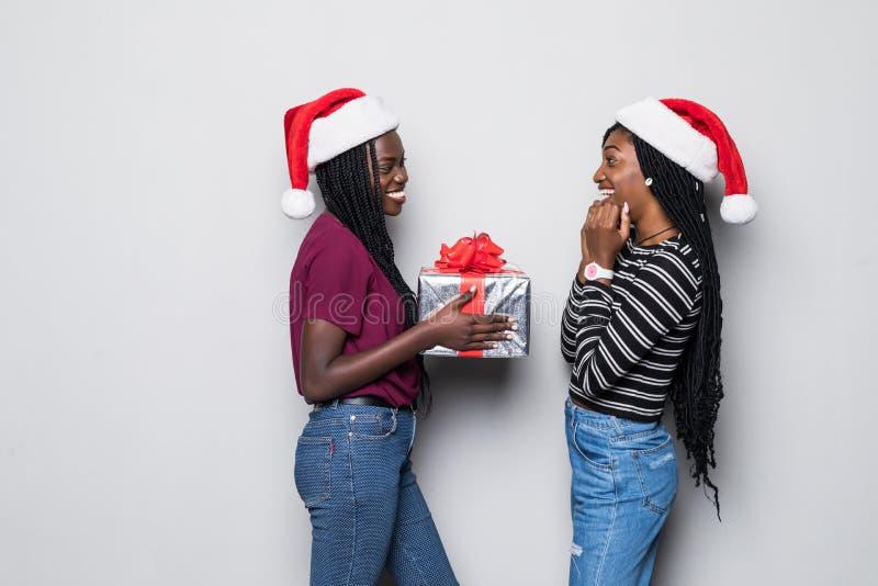 年轻两名非洲妇女画象有圣诞老人帽子在灰色背景隔绝的份额礼物的 免版税图库摄影