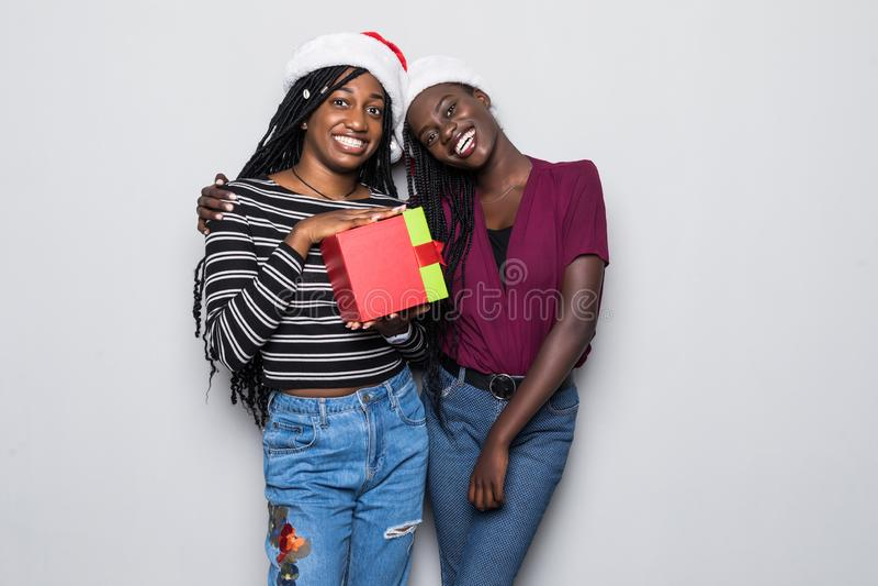 年轻两名非洲妇女画象有圣诞老人帽子的有在灰色背景隔绝的礼物的 免版税图库摄影