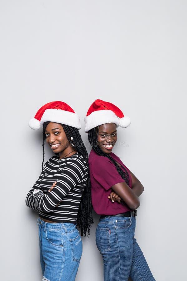 年轻两名非洲妇女画象有紧接站立圣诞老人的帽子的隔绝在灰色背景 免版税库存照片