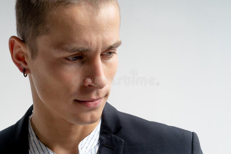 年轻严肃的人接近的画象黑衣服的与耳环被隔绝在白色背景,您的copyspace 免版税库存图片