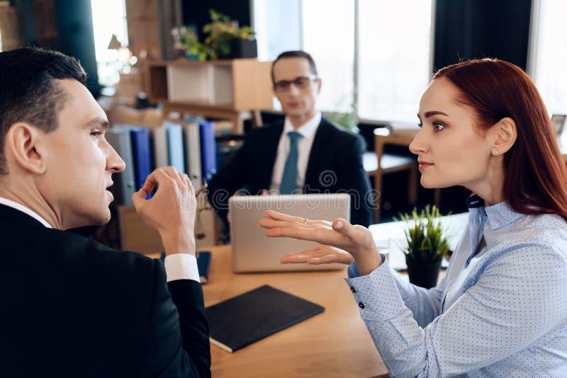 年轻严肃的夫妇咨询,坐在离婚提倡者办公室 成人夫妇离婚 免版税图库摄影