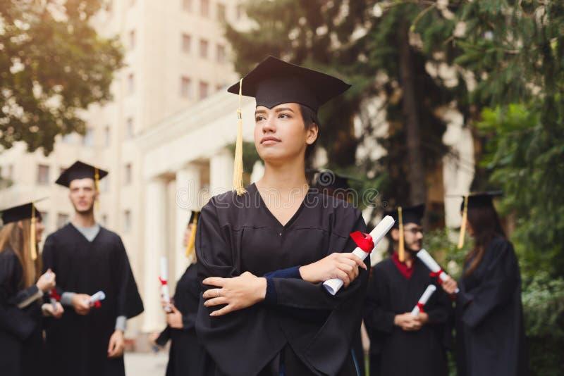 年轻严肃的妇女在她的毕业典礼举行日 免版税库存图片