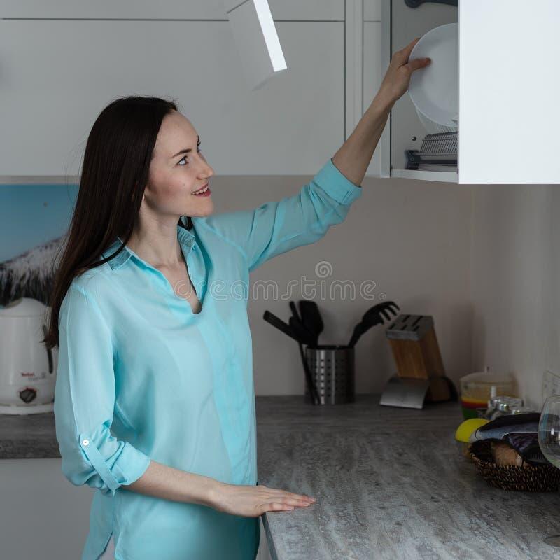 年轻主妇在干燥机架架子上把干净的盘放在白色厨房内部,家务概念 库存照片