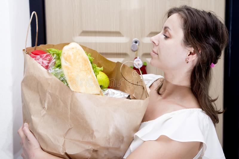 年轻主妇带来了包含从杂货店的家庭帐面袋子菜 妇女用在房子的门背景的食物  免版税图库摄影