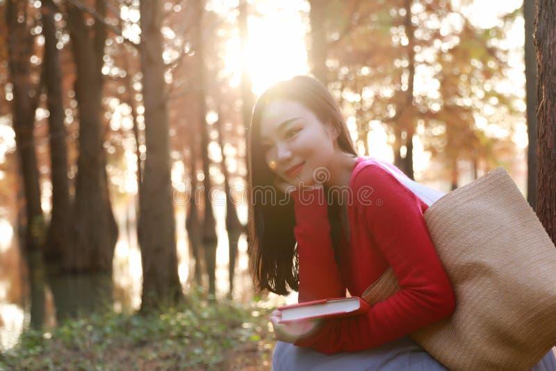 年轻亚洲中国妇女读书在秋天水红色森林里 免版税库存照片