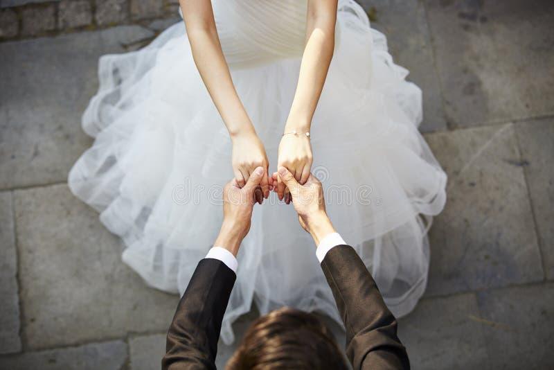 年轻亚洲举行手和跳舞的新娘和新郎 免版税库存图片