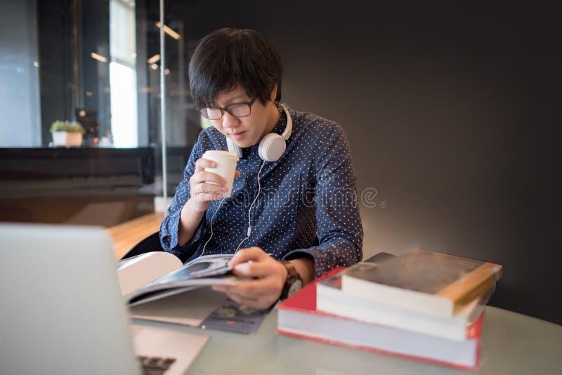 年轻亚洲人大学生阅读书在图书馆里 免版税库存图片