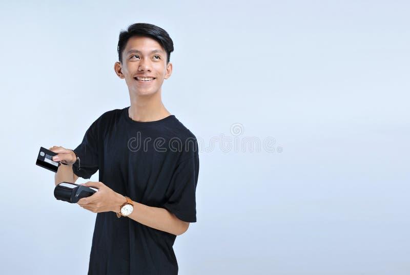 年轻亚洲人重击一张信用卡/一借记卡和看拷贝空间 免版税图库摄影
