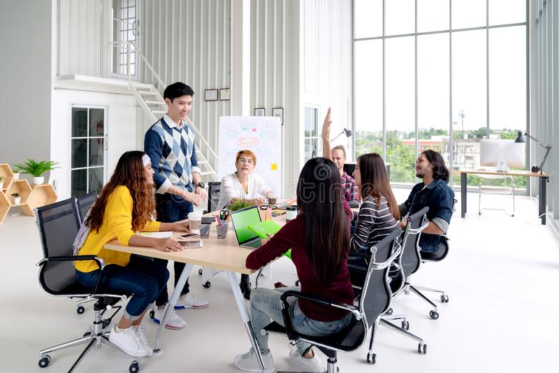 年轻亚洲创造性的队谈话,微笑和笑群策群力,分享或者训练在会议或车间的小组在办公室 免版税库存图片