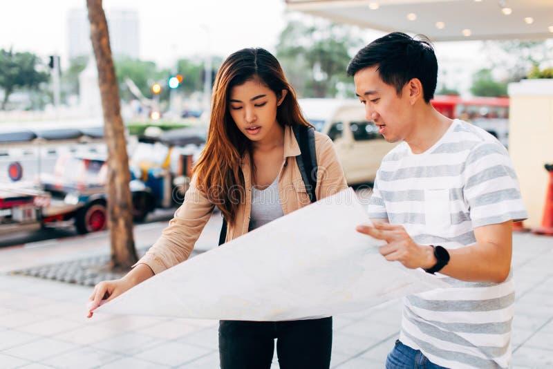 年轻亚洲加上在街道上的地图 免版税库存图片