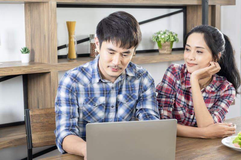 年轻亚洲可爱的在家在网上购物的夫妇观看的膝上型计算机办公室 图库摄影