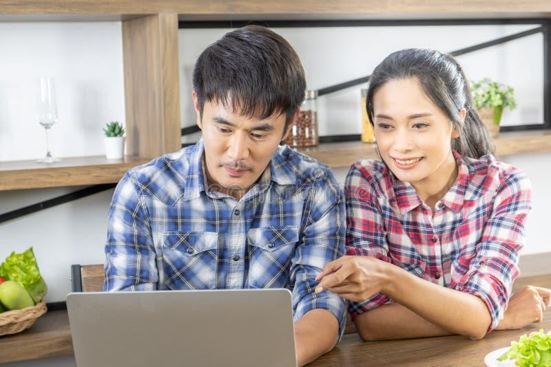 年轻亚洲可爱的在网上购物的夫妇观看的膝上型计算机 库存图片