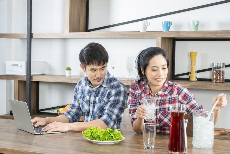 年轻亚洲可爱的夫妇饮用的咖啡用牛奶在厨房里在家 库存照片