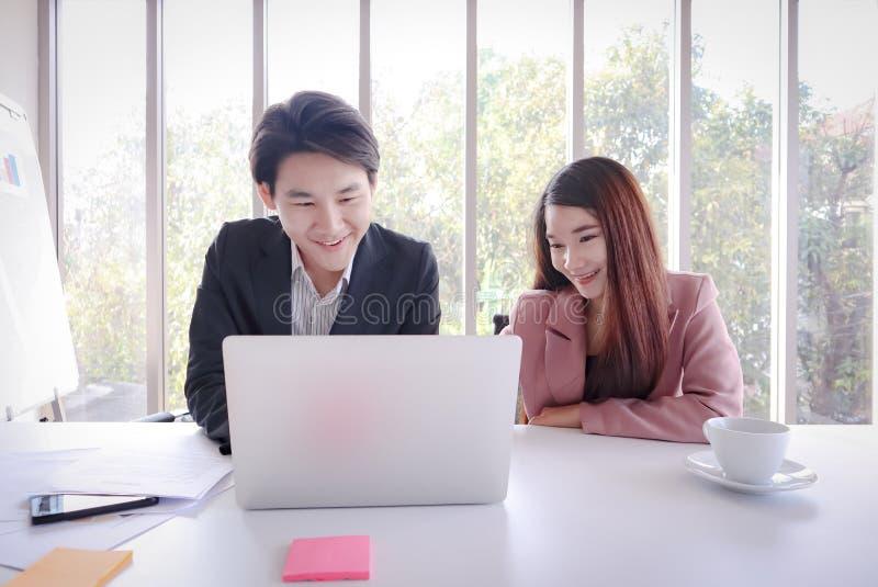 年轻亚洲商人与膝上型计算机一起使用在办公室 免版税库存照片