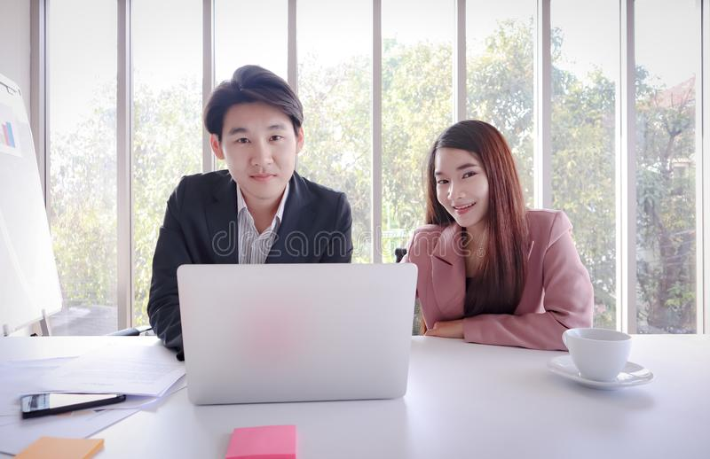 年轻亚洲商人与膝上型计算机一起使用在办公室 库存照片