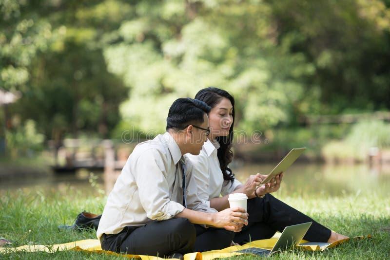 年轻亚洲商人和妇女愉快的面孔放松坐饮用的c 免版税图库摄影
