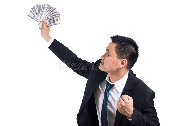 年轻亚洲商人庆祝成功 举行美元钞票愉快和微笑的商人 免版税库存图片