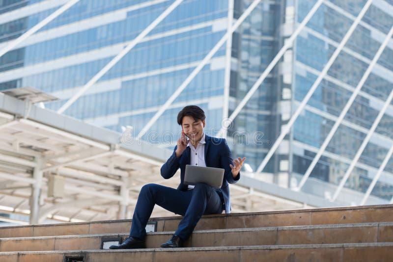 年轻亚洲商人愉快谈话在手机和lookin 免版税库存图片