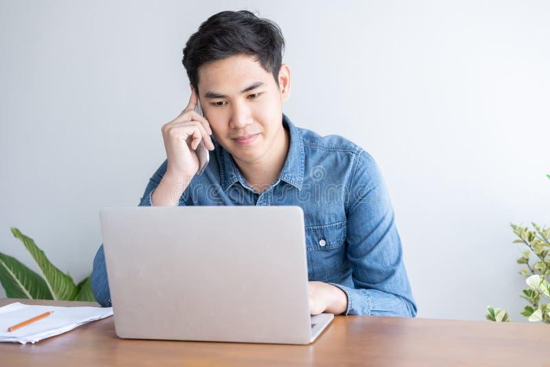 年轻亚洲商人穿谈话在手机和研究他的膝上型计算机的蓝色衬衣在办公室 免版税图库摄影