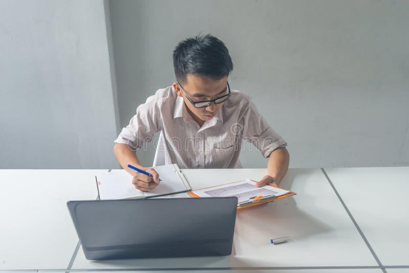 年轻亚洲商人读的财政报告和注意 免版税图库摄影