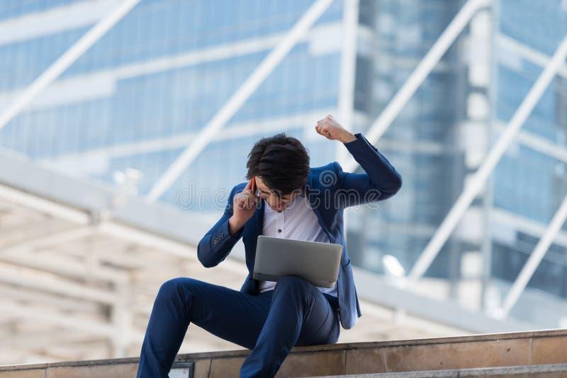 年轻亚洲商人谈话在有严肃的f的手机 免版税库存照片