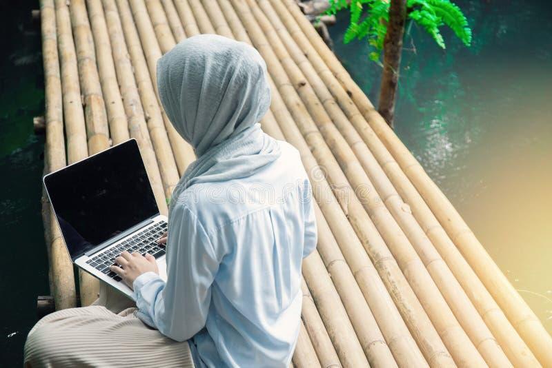 年轻亚洲回教妇女制定出在绿色自然公园概念的办公室冷颤在别致的工作场所的女性企业家工作的, 免版税库存图片