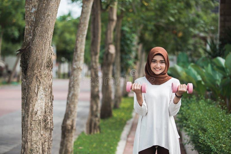 年轻亚洲回教妇女行使室外 免版税图库摄影