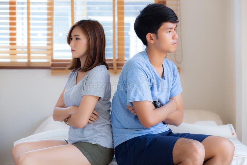 年轻亚洲夫妇关系有在床上的问题在卧室在家,有的家庭冲突论据以不快乐 库存图片