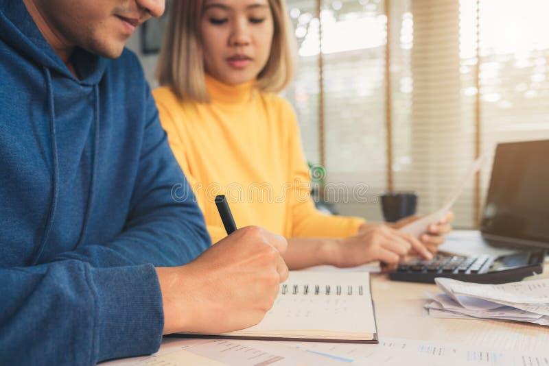 年轻亚洲夫妇处理的财务,回顾他们的银行帐户使用便携式计算机和计算器在现代家 免版税图库摄影