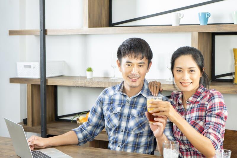 年轻亚洲夫妇是愉快一起烹调,两个家庭互相帮助准备在厨房里烹调 库存照片