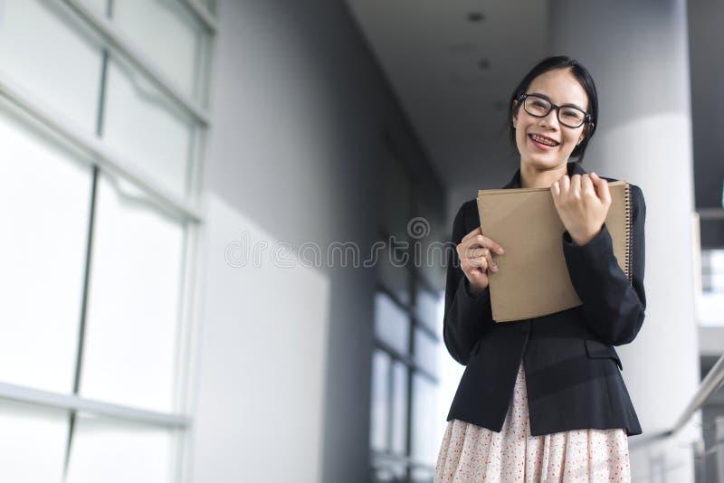 年轻亚洲女商人穿戴衣服待办卷宗文件 库存照片