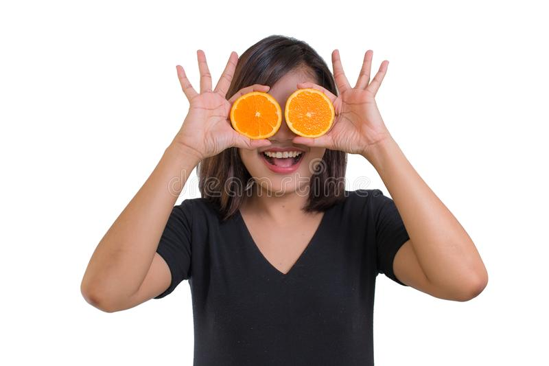 年轻亚洲女服黑色衬衣画象  拿着在白色背景在她的眼睛和微笑前面的橙色切片隔绝的 库存照片