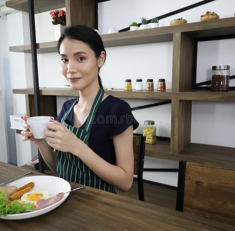 年轻亚洲妇女举行杯子无奶咖啡 免版税库存照片