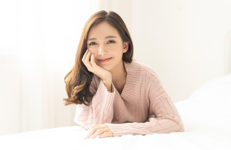 年轻亚洲妇女微笑友好和看照相机画象在客厅 妇女的面孔特写镜头 r 库存照片