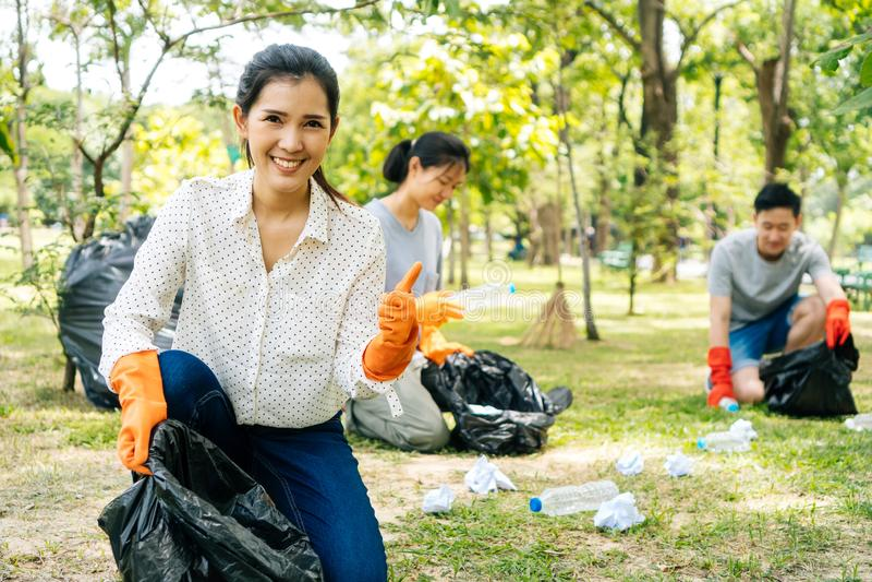 年轻亚洲妇女微笑,给与收集在垃圾袋的朋友的赞许垃圾在公园 免版税图库摄影