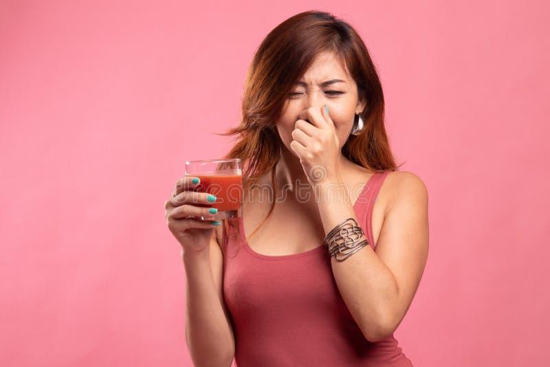 年轻亚洲妇女怨恨西红柿汁 免版税库存图片