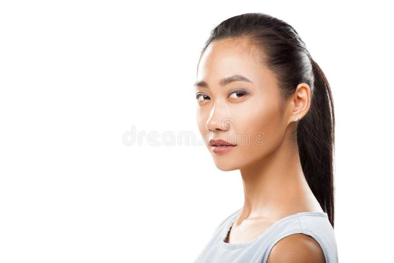 年轻亚洲妇女特写镜头转动了头和看照相机 图库摄影