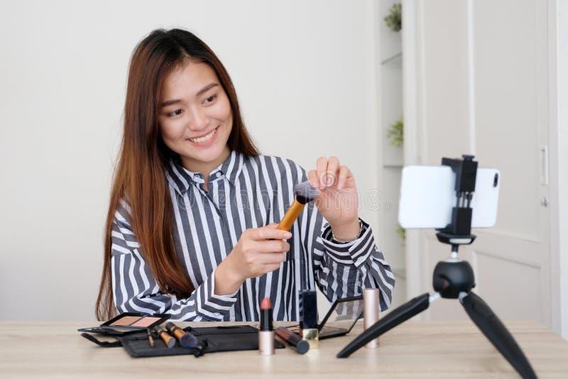 年轻亚洲妇女秀丽博客作者陈列如何组成录影tu 免版税库存照片
