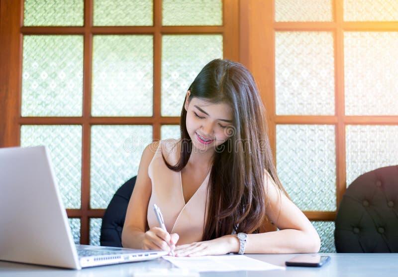 年轻亚洲妇女自由职业者微笑和使用labtop和写笔记在大学图书馆 免版税库存图片