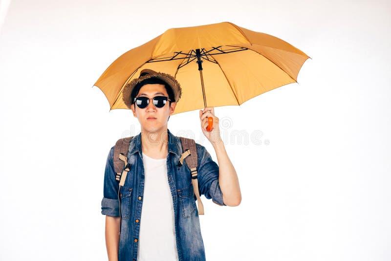 年轻亚洲旅游举行的伞被隔绝在白色背景 单独和正在寻找伙伴旅行 图库摄影