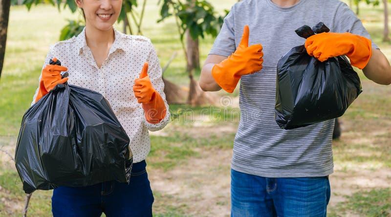 年轻亚洲男性和女性夫妇志愿者有给赞许的手套的,当收集垃圾废物入垃圾袋时 免版税库存照片