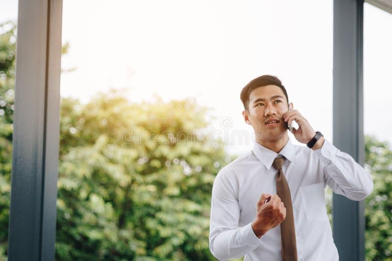 年轻亚洲英俊的商人谈话在电话和幸福工作的 免版税库存图片