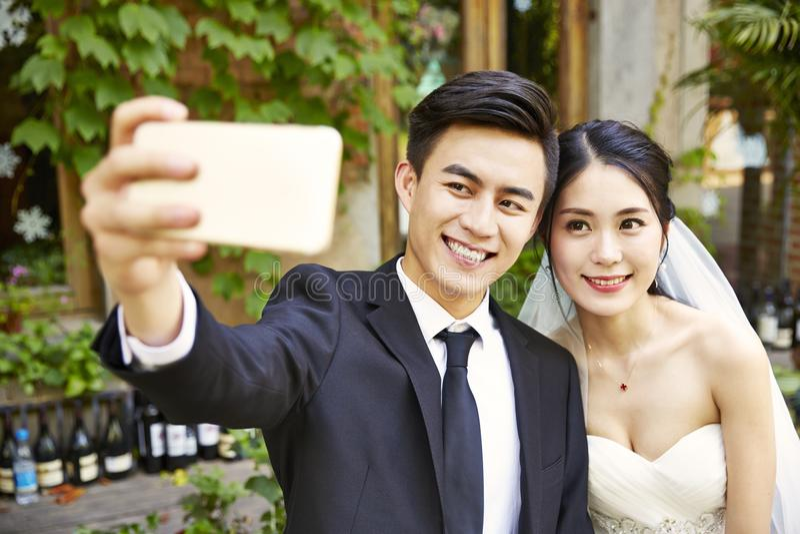 年轻亚洲采取selfie的新娘和新郎 免版税库存照片
