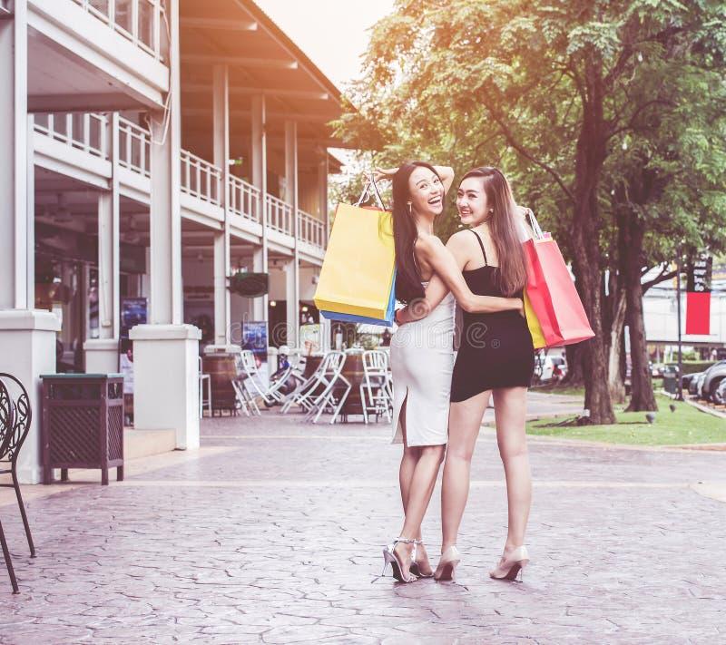 年轻亚洲 有长的美丽的头发的微笑的妇女在五颜六色的白色和黑外套的愉快的面孔塑造拿着袋子的构成  免版税库存照片