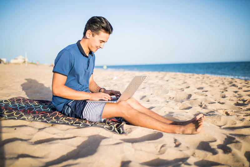年轻亚裔人与在热带海滩的便携式计算机一起使用 游人 库存图片