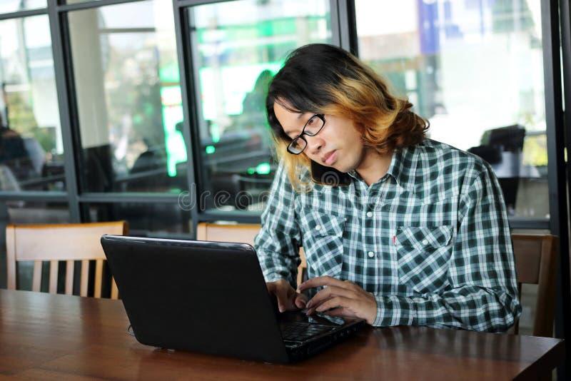 年轻亚裔人与膝上型计算机和流动巧妙的电话一起使用在办公室 免版税库存照片