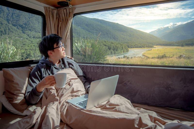 年轻亚裔人饮用的咖啡与膝上型计算机一起使用在露营车VA 免版税库存照片