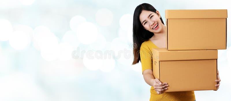 年轻亚裔企业家愉快的微笑的和举行的或者运载的堆画象箱子在手上在被弄脏的背景 免版税图库摄影