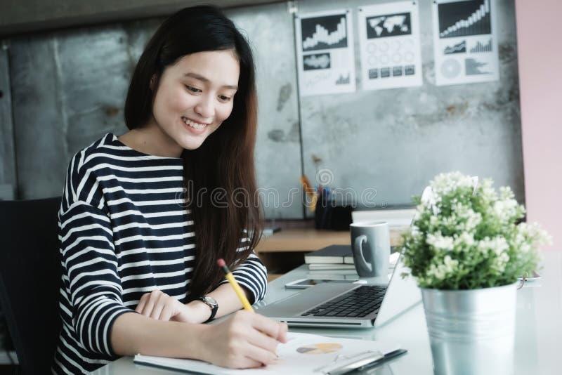年轻亚裔办公室妇女与便携式计算机一起使用在书桌  库存图片