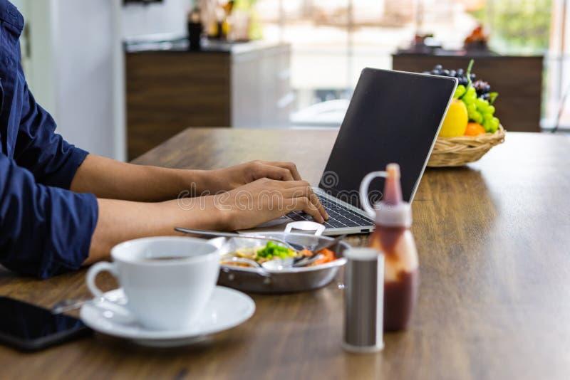 年轻亚裔吃在木桌上的人运转的膝上型计算机特写镜头早餐饮用的咖啡 免版税库存图片